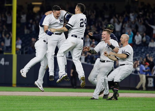 New York Yankees' Gio Urshela celebrates with teammates after hitting an RBI single during the ninth inning of the team's game against the Tampa Bay Rays on Friday, May 17, 2019, in New York. The Yankees won 4-3.