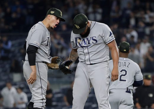 Tampa Bay Rays' Willy Adames, left, talks to relief pitcher Jose Alvarado during the ninth inning of the team's game against the New York Yankees on Friday, May 17, 2019, in New York. The Yankees won 4-3.