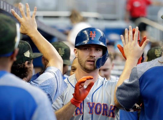 New York Mets' Pete Alonso is congratulated in the dugout after hitting a solo home run during the second inning of the team's game against the Miami Marlins, Friday, May 17, 2019, in Miami.