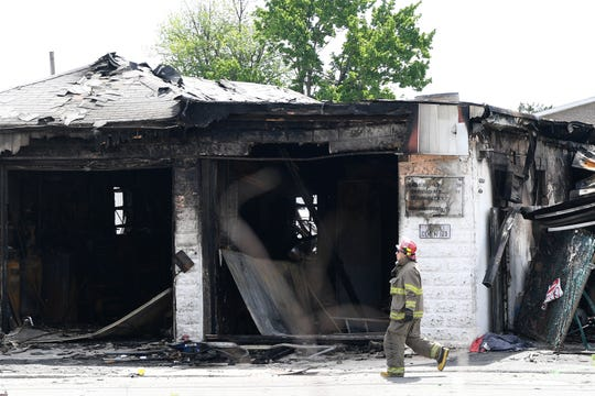 A firefighter walks past Quality Auto Body in Wood-Ridge on Saturday, May 18, 2019. Quality Auto Body was destroyed by a fire last night.