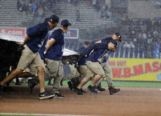 Members of the grounds crew cover the field during a rain delay in the eighth inning of a game between the New York Yankees and the Tampa Bay Rays at Yankee Stadium on Friday, May 17, 2019, in New York.