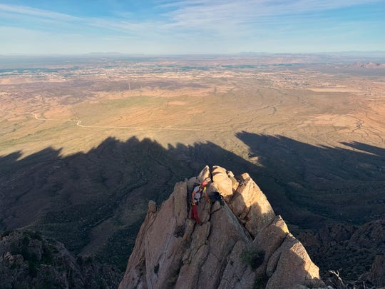 Kevin Boyko summits Razorback Peak at sunrise with the shadow of the Organ Mountains on the valley floor.