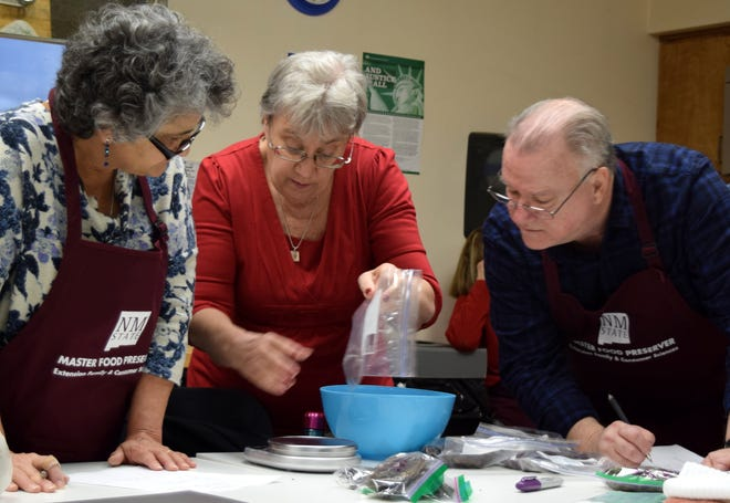 Master Food Preservation trainers Barbara Talent of Albuquerque, Cindy Bighorse of Saginaw, Texas, and Michael Fox of Fort Worth, Texas, weigh ingredients for a recipe.