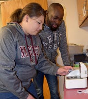 New Mexico State University graduate students Rebecca Mijares and Adetoye Abodunrin measure the water content of a food sample during the Master Food Preservation train-the-trainer lab.