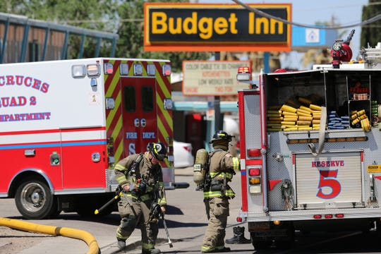 Las Cruces firefighters put away gear after dousing a fire in a room at the Budget Inn, 2255 W. Picacho Ave., on Saturday, May 18, 2019.