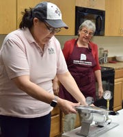 Nancy Flores, New Mexico State University Extension food technology specialist, demonstrates how to test a pressure canner valve to ensure it functions correctly before starting the canning process. Cindy Bighorse from Saginaw, Texas, watches.