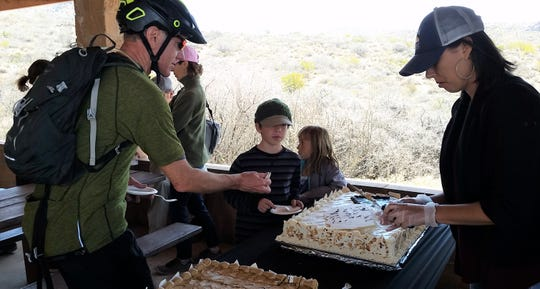 Bicyclist Philip Simpson, left, of the Southern New Mexico Trail Alliance gets a piece of cake from Grecia Nuñez of the New Mexico Wilderness Alliance during a March 21, 2019 event celebrating the creation of wilderness within Organ Mountains-Desert Peaks National Monument. Wilderness was created just month's before the monument's fifth anniversary.