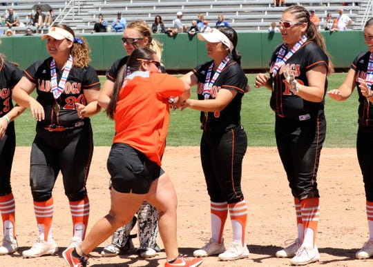 Artesia head coach Sandra Pulido high-fives her players after Saturday's championship game.