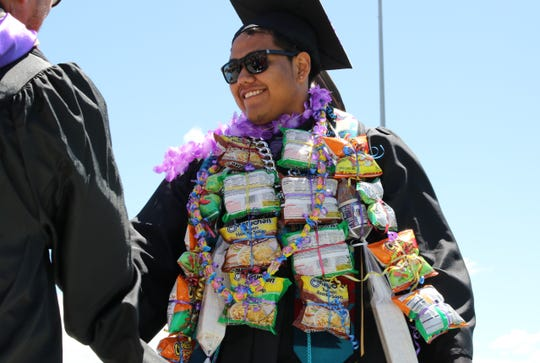Jeremiah Slim shakes the hand of a Navajo Preparatory School administration official during the school's graduation ceremony on May 18 in Farmington.
