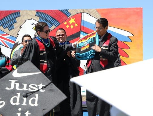 Navajo Nation President Jonathan Nez, right, receives a Pendleton blanket from Navajo Preparatory School at the school's graduation ceremony on May 18 in Farmington.