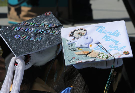 Messages adorn the caps of two Navajo Preparatory School graduates during the commencement ceremony on May 18 in Farmington.