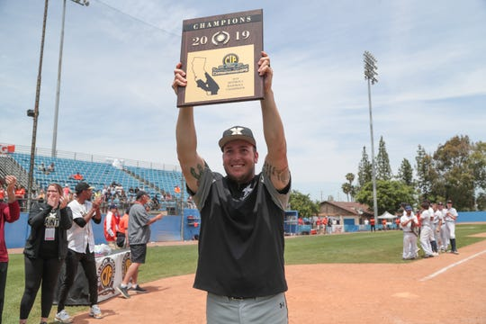 Xavier Prep head coach Andrew Clark lifts up the CIF Championship plaque after defeating Poly Pasadena in the CIF-SS Division 5 championships, Riverside, Calif., May 18, 2019.