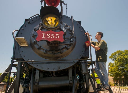 "Zach Panici paints the Frisco 1355 locomotive, dubbed ""The Pride of Pensacola,"" in May along Garden Street as part of his work toward becoming an Eagle Scout."