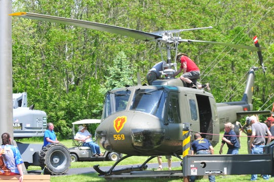 The rotors are attached to the Huey helicopter in preparation for it being lifted onto its 20-foot platform.
