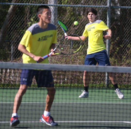Pittsford Sutherland's Brady Thyroff, right, returns serve as he and doubles partner Alan Tu, left, take on Nate Allen and Trey Kernan of Penfield.