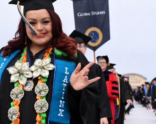 A student waves at the camera during the CSUMB graduation from the College or Arts, Humanities and Social Sciences on Saturday, May 18.
