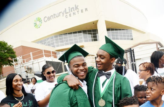 Bossier's Kaalas Roots (right) enjoys a laugh with a friend outside the CenturyLink Center following his Saturday graduation.