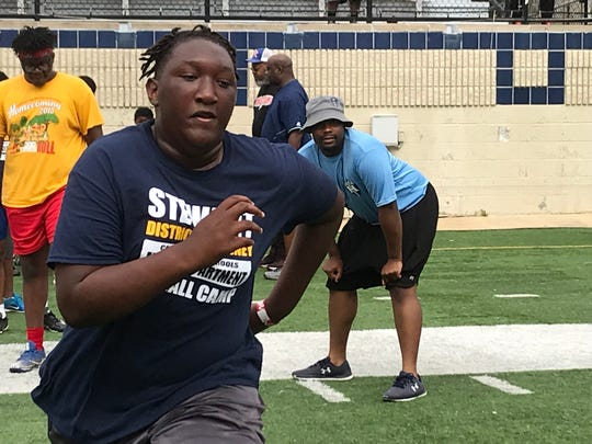 A teenager is put through drills by a Huntington assistant coach during Saturday's Caddo DA football camp at Independence Stadium.