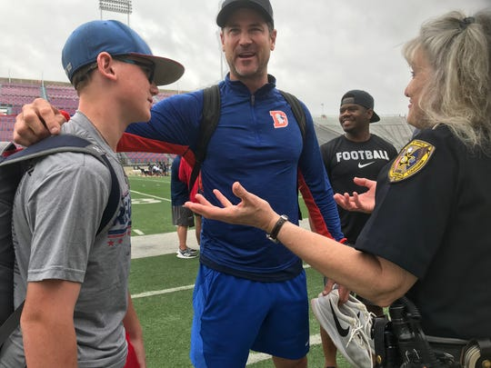 Former LSU quarterback Josh Booty shares a laugh with his son, Parker, and a Caddo deputy.