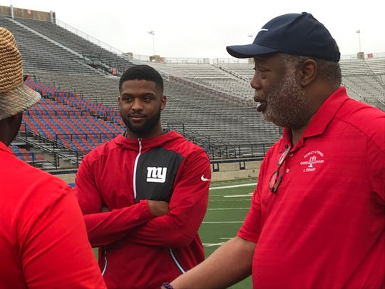 Caddo District Attorney James Stewart (right) visits with former West Monroe standout Michael Hunter during Saturday's camp at Independence Stadium.