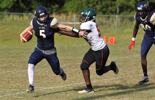 St. John Paul II quarterback Michael Glaze tries to escape a tackle as FAMU DRS beat St. John Paul II 30-0 during a spring football scrimmage on May 17, 2019.