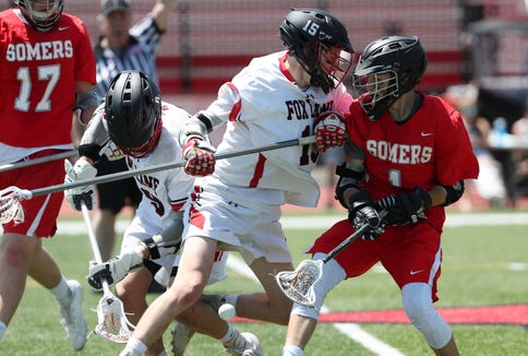 Fox Lane's Ryan Feeley (15) knocks the ball away from Somers'  Daniel Rios (1) during boys lacrosse playoff action at Fox Lane High School in Bedford May 16, 2019. Fox Lane won the game 12-10.
