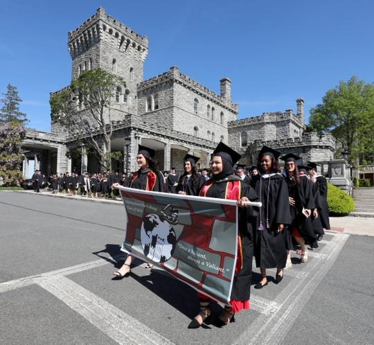 Jasmine Maria Villegas, the Senior Class President and Asma Syed Alirahi, the Student Body President, carry the class banner as Manhattanville College celebrated their 178th commencement on their campus in Purchase, May 18, 2019.