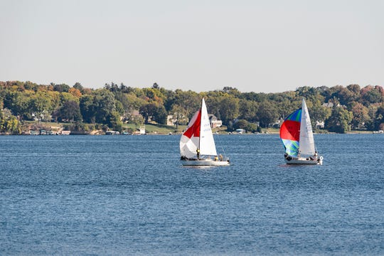 Seen from the University of Wisconsin-Madison shoreline, a pair of sailboats glide across the open water of Lake Mendota during a sunny autumn morning on Oct. 8, 2017.