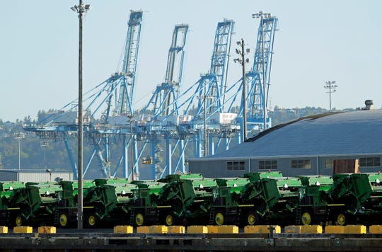 FILE - In this May 10, 2019, file photo John Deere Agricultural machinery made by Deere & Company sits staged for transport near cranes at the Port of Tacoma in Tacoma, Wash. Deere's fiscal second-quarter earnings were a mixed bag and the agricultural equipment maker lowered its full-year outlook as the trade war between the U.S. and China intensifies and conditions in the agricultural sector soften.
