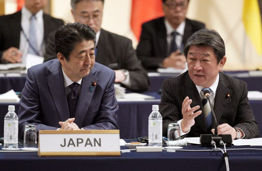 FILE - In this  Jan. 19, 2019, file photo, Japan's Prime Minister Shinzo Abe, left, and Minister of Economy, Trade, and Industry Toshimitsu Motegi, right, share a light moment during an opening session of the Comprehensive and Progressive Trans-Pacific Partnership (CPTPP) in Tokyo. Motegi said Friday, May 17, 2019 Washington won't be demanding any numerical restrictions on Japanese auto exports to the U.S., speculated by media reports as a possibility.