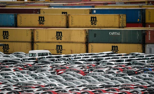 Cars for export and import are stored in front of containers on Thursday, May 16, 2019 at the harbor in Bremerhaven, Germany, with 2 million vehicles per annum one of the largest automobile hubs in the world. US President Donald Trump is delaying any decision to impose tariffs on car and auto-part imports for now.