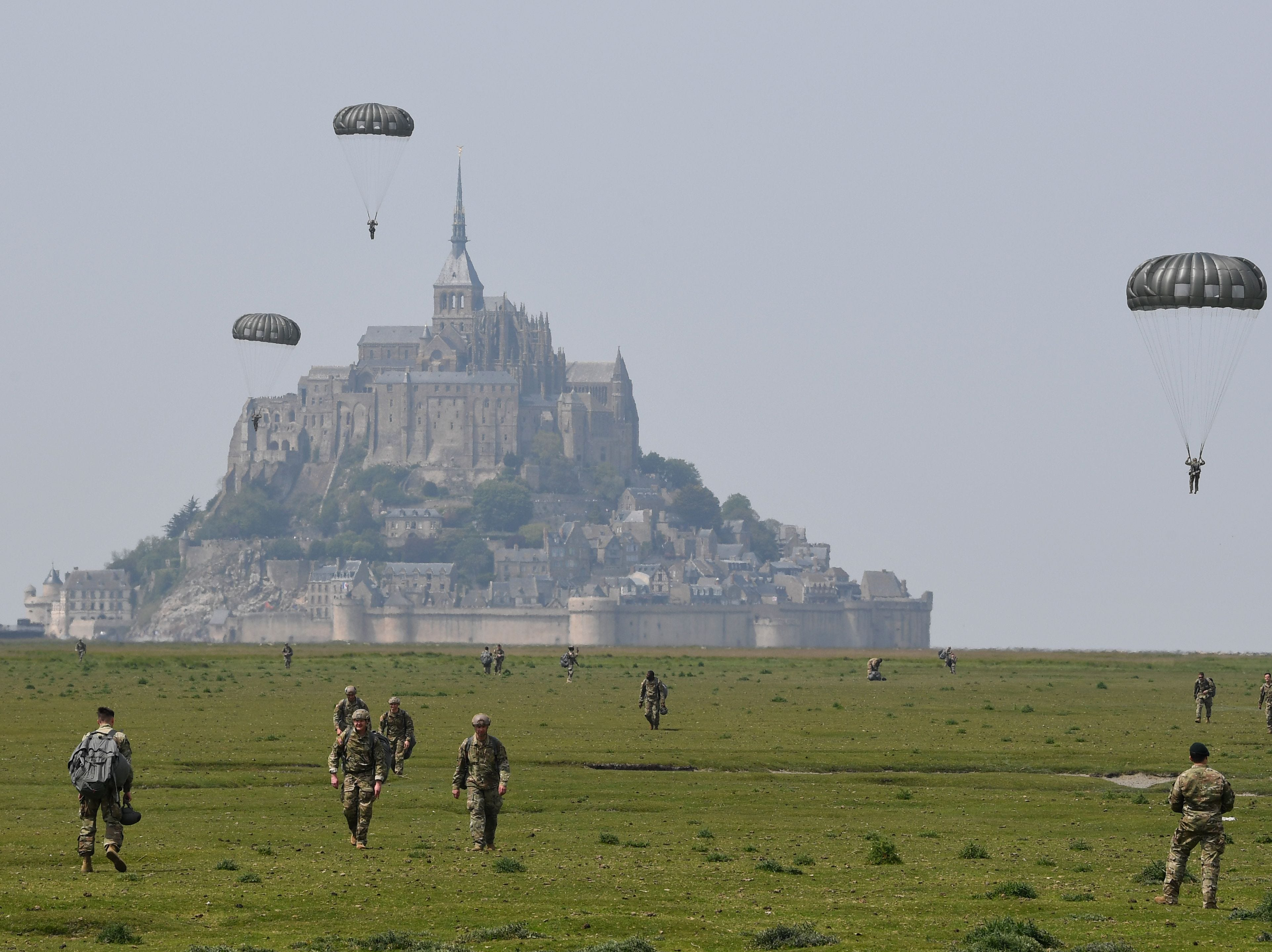 US paratroopers walk back after jumping over Le Mont-Saint-Michel, north-western France on May 18, 2019, less than three weeks before the 75th anniversary of the D-Day landings. In what remains the biggest amphibious assault in history, some 156,000 Allied personnel landed in France on June 6, 1944. An estimated 10,000 Allied troops were left dead, wounded or missing, while Nazi Germany lost between 4,000 and 9,000 troops, and thousands of French civilians were killed. The 75th anniversary of the D-Day landings will fall on June 6, 2019.