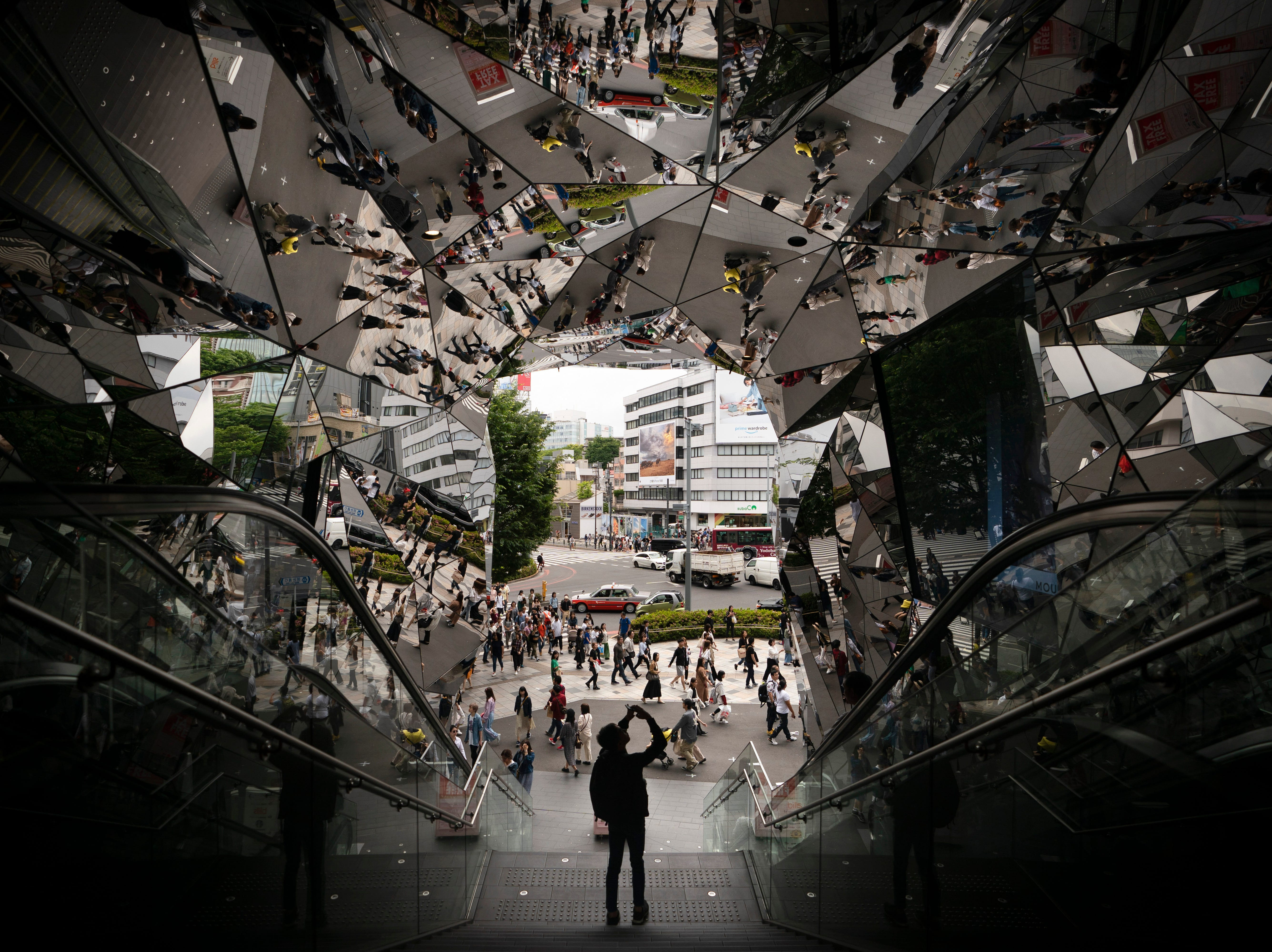 A tourist takes pictures in the entrance way to a shopping mall decorated with mirrors Saturday, May 18, 2019, in Harajuku district of Tokyo.