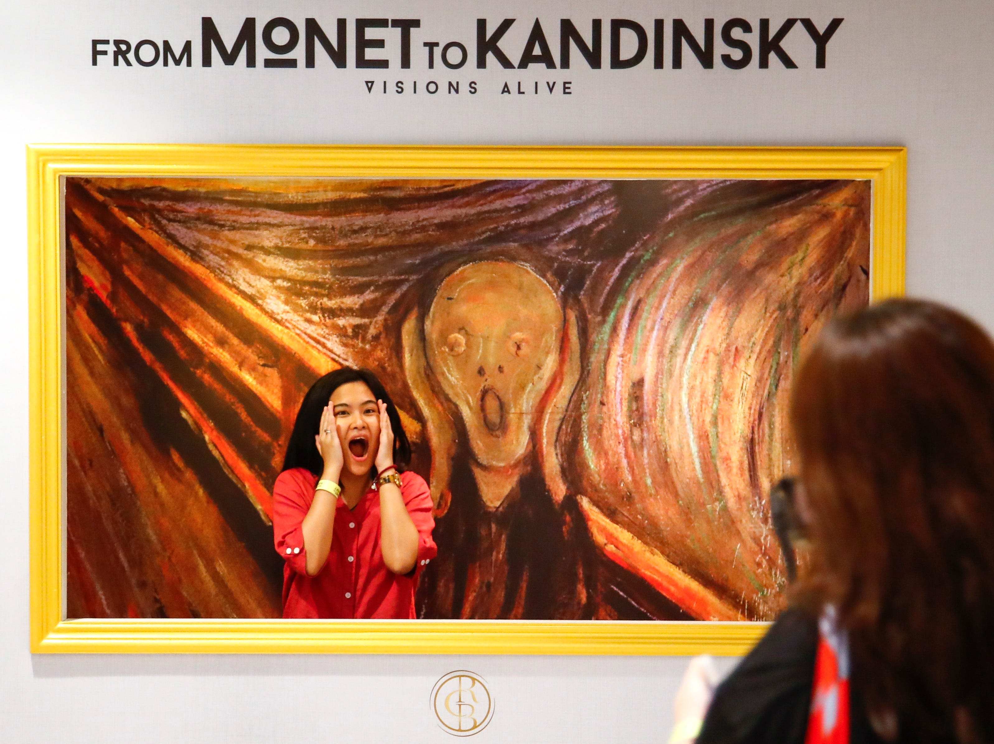 A visitor poses in front of a reproduction of 'The Scream' by Norwegian painter Edvard Munch (1863-1944) at the 'From Monet to Kandinsky' exhibit in Bangkok, Thailand on May 18, 2019. The multimedia exhibit showcases over 1,500 masterpieces from 16 European artists from the late 19th and early 20th century projected on walls and accompanied with music.