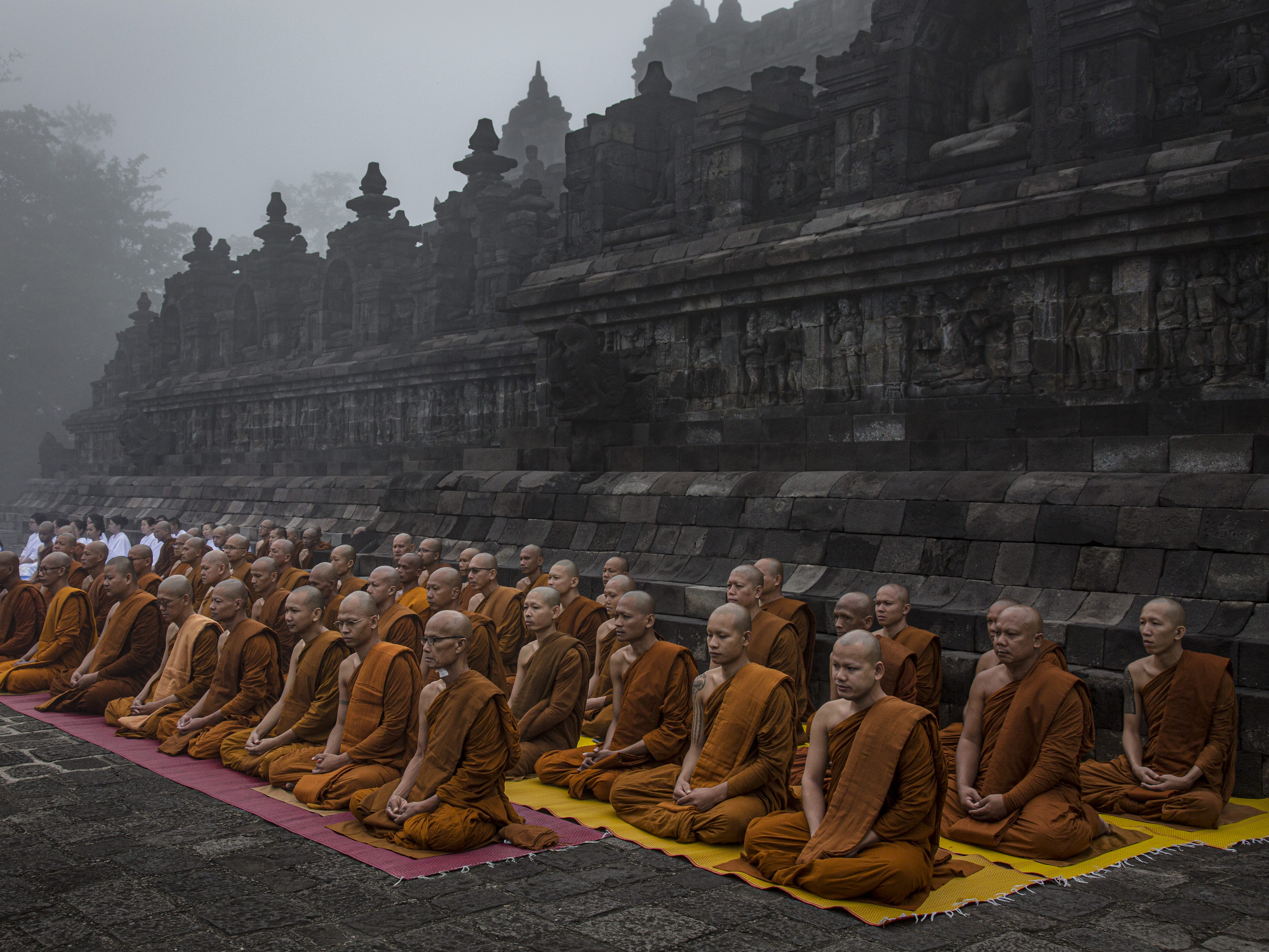 Buddhist monks pray at Borobudur temple during celebrations for Vesak Day on May 18, 2019 in Magelang, Central Java, Indonesia. Buddhists in Indonesia celebrate Vesak at the Borobudur temple annually, which makes it the most visited tourist attraction in Indonesia. It is observed during the full moon in May or June, with the ceremony centered at three Buddhist temples by walking from Mendut to Pawon and ending at Borobudur. The stages of life of Buddhism's founder, Gautama Buddha, which are celebrated at Vesak are his birth, enlightenment to Nirvana, and his passing (Parinirvana).