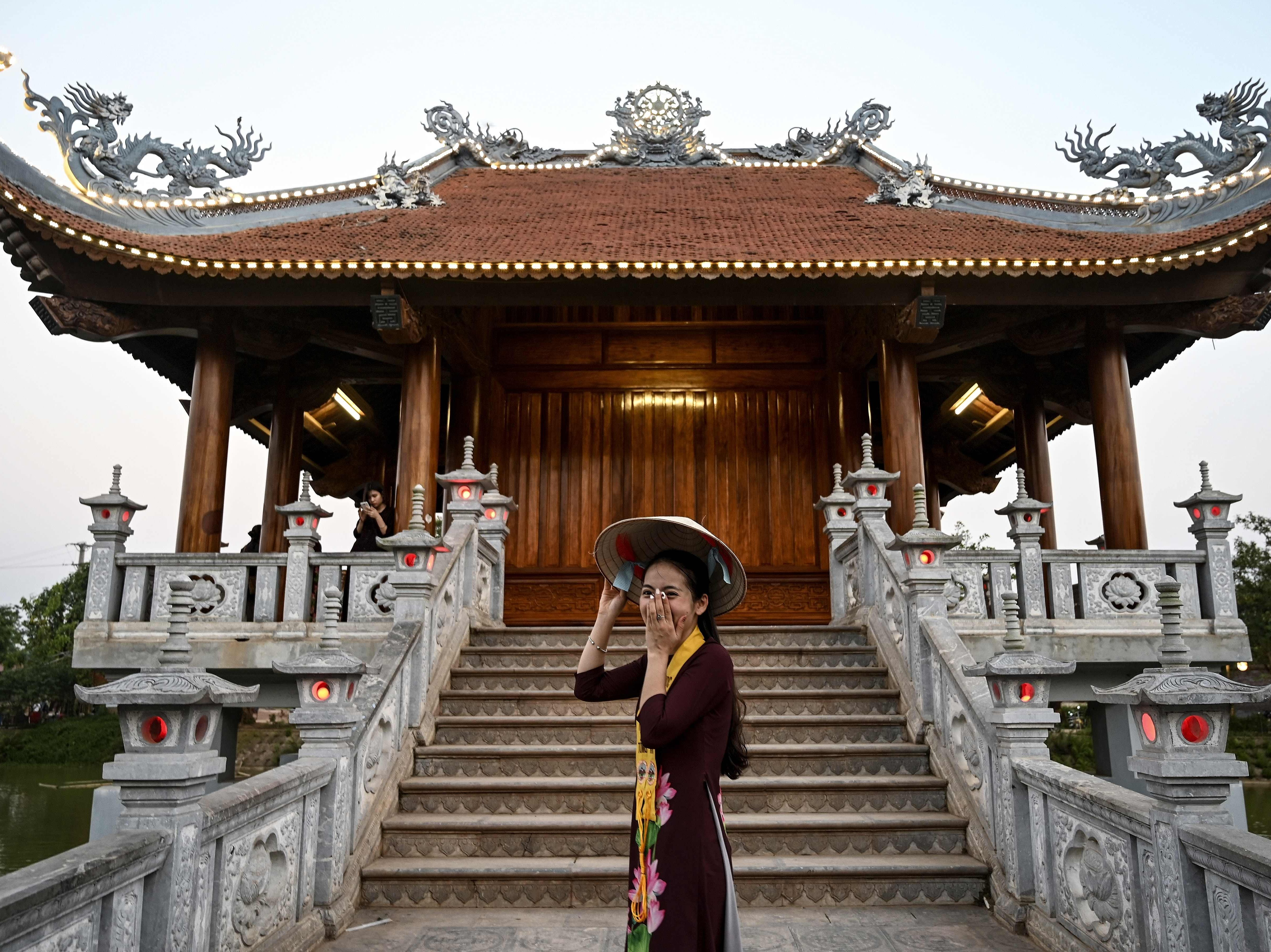 A Vietnamse woman poses for a photographs at the Khai Nguyen pagoda in Son Tay on the outskirts of Hanoi on May 18, 2019, on the eve of the Vesak day or Buddha day festival, marking the birth of Gautama Buddha, his attaining enlightenment, and his passing away. - Buddhists commemorate the birth of Buddha, his attaining enlightenment and death on the day of the full moon, which falls on May 18 this year.