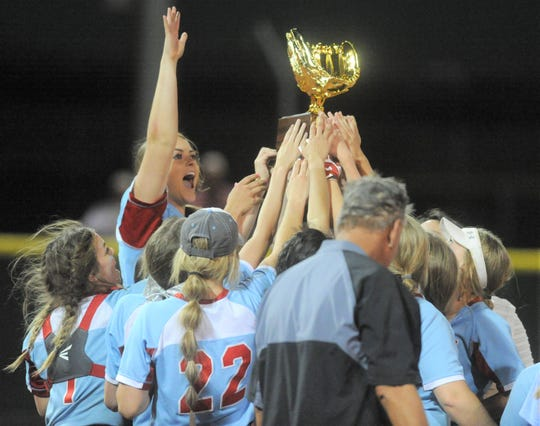 The Gail Borden County softball team celebrate with its Region I-1A championship trophy May 18 at First United Park in Lubbock.