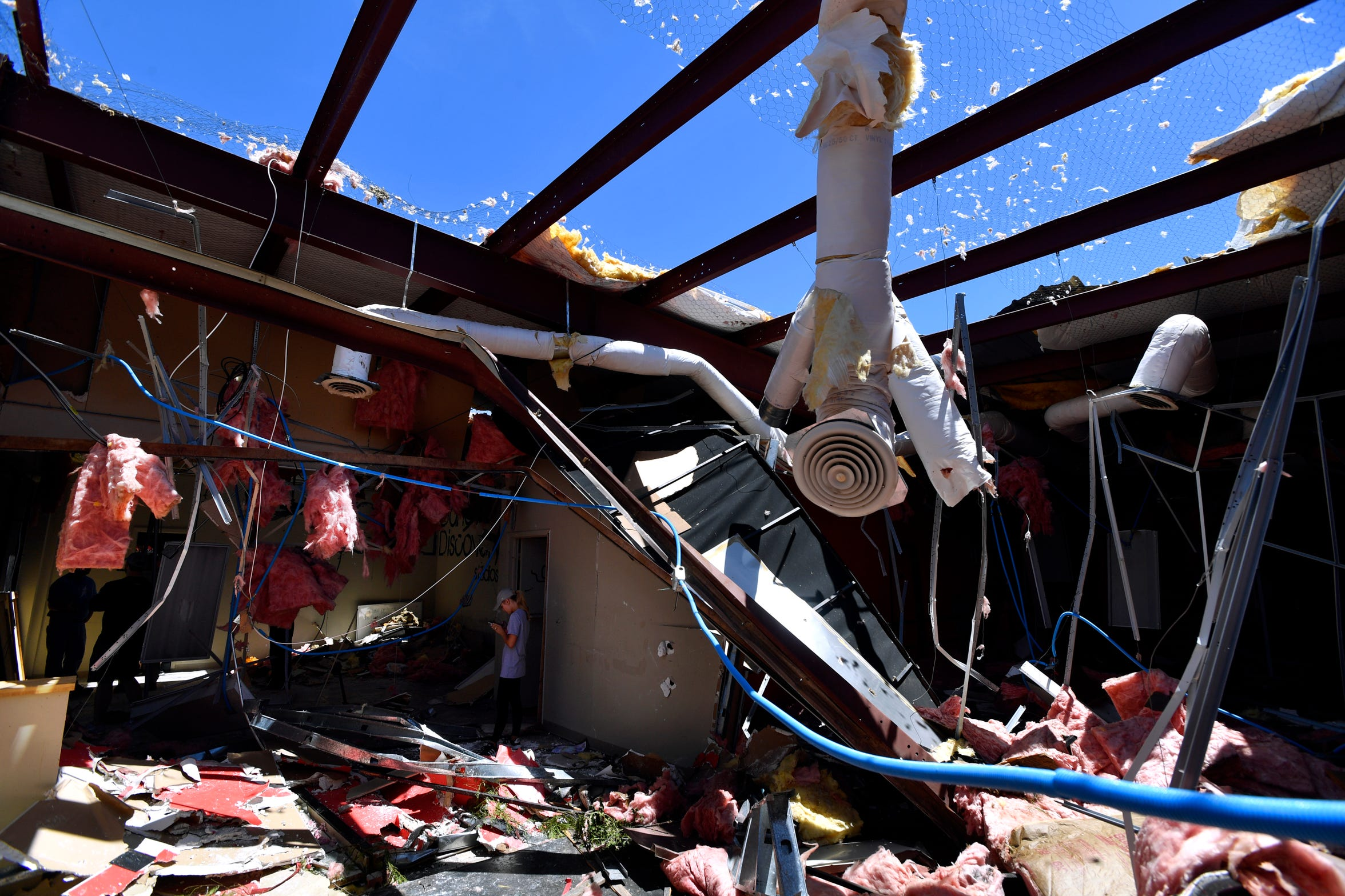 The day after a tornado destroyed her business, Kirby Altimont answers a text message inside the remains of Dance Discovery Studios at 3347 S. Second St. She and her mother, Teri Wilkerson, cleaned up but moved to 209 S. Danville Drive 107 days later.