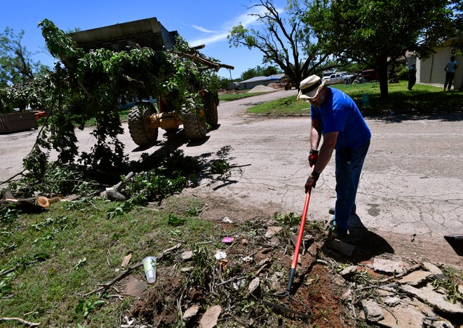 David Cline rakes debris while a city of Abilene front-end loader scoops up a pile of tree limbs at the intersection of South Second and Carl streets Sunday. Cleanup began in earnest the day after a confirmed EF-2 tornado struck Abilene with volunteers such as Cline turning out to help their neighbors.