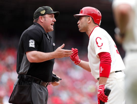 Cincinnati Reds first baseman Joey Votto (right) talks with with home plate umpire Dan Bellino (2) after striking out against the Los Angeles Dodgers during the first inning at Great American Ball Park.