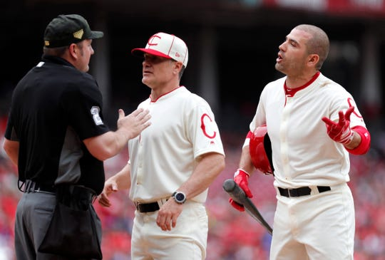 Cincinnati Reds first baseman Joey Votto (right) talks with with home plate umpire Dan Bellino (left) after striking out during the first inning against the Los Angeles Dodgers at Great American Ball Park. Reds manager David Bell (middle) listens in.