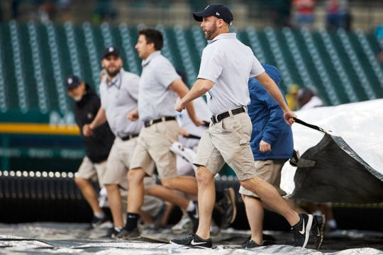 Grounds crew pull the tarp onto the field during the seventh inning at Comerica Park on Sunday.