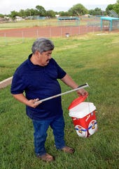 Hector Aguilar uses a claw grabber extension to remove a hypodermic needle from one of the baseball fields at Atrisco Park. The little league park is fighting a battle against discarded syringes with attached hypodermic needles amid the region's outgoing opioid epidemic.