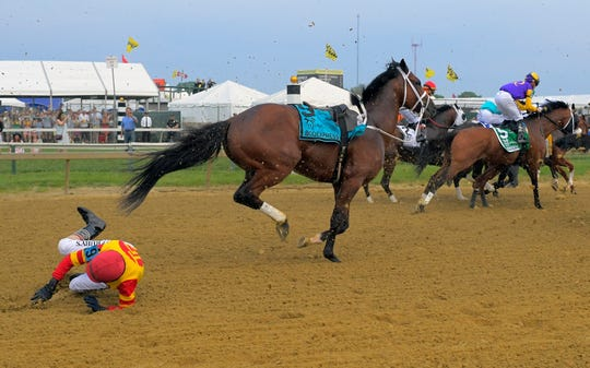Jockey John Velazquez tumbles to the track after being thrown by Bodexpress as the field breaks from the starting gate.