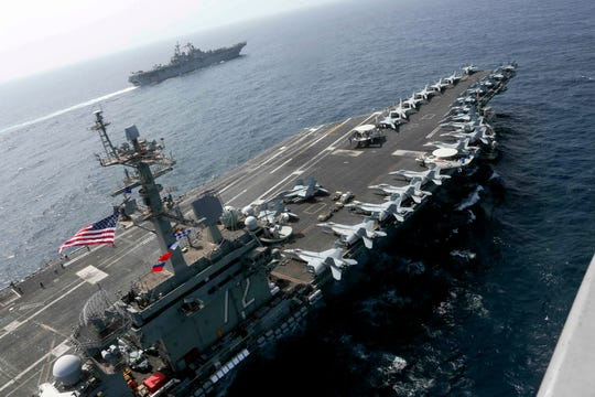 In this Friday, May 17, 2019, photo released by the U.S. Navy, the USS Abraham Lincoln sails in the Arabian Sea near the amphibious assault ship USS Kearsarge.