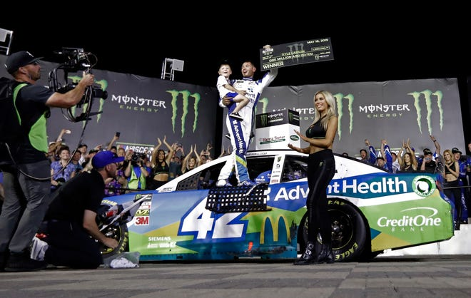 Kyle Larson celebrates in Victory Lane after winning the NASCAR All-Star Race at Charlotte Motor Speedway.