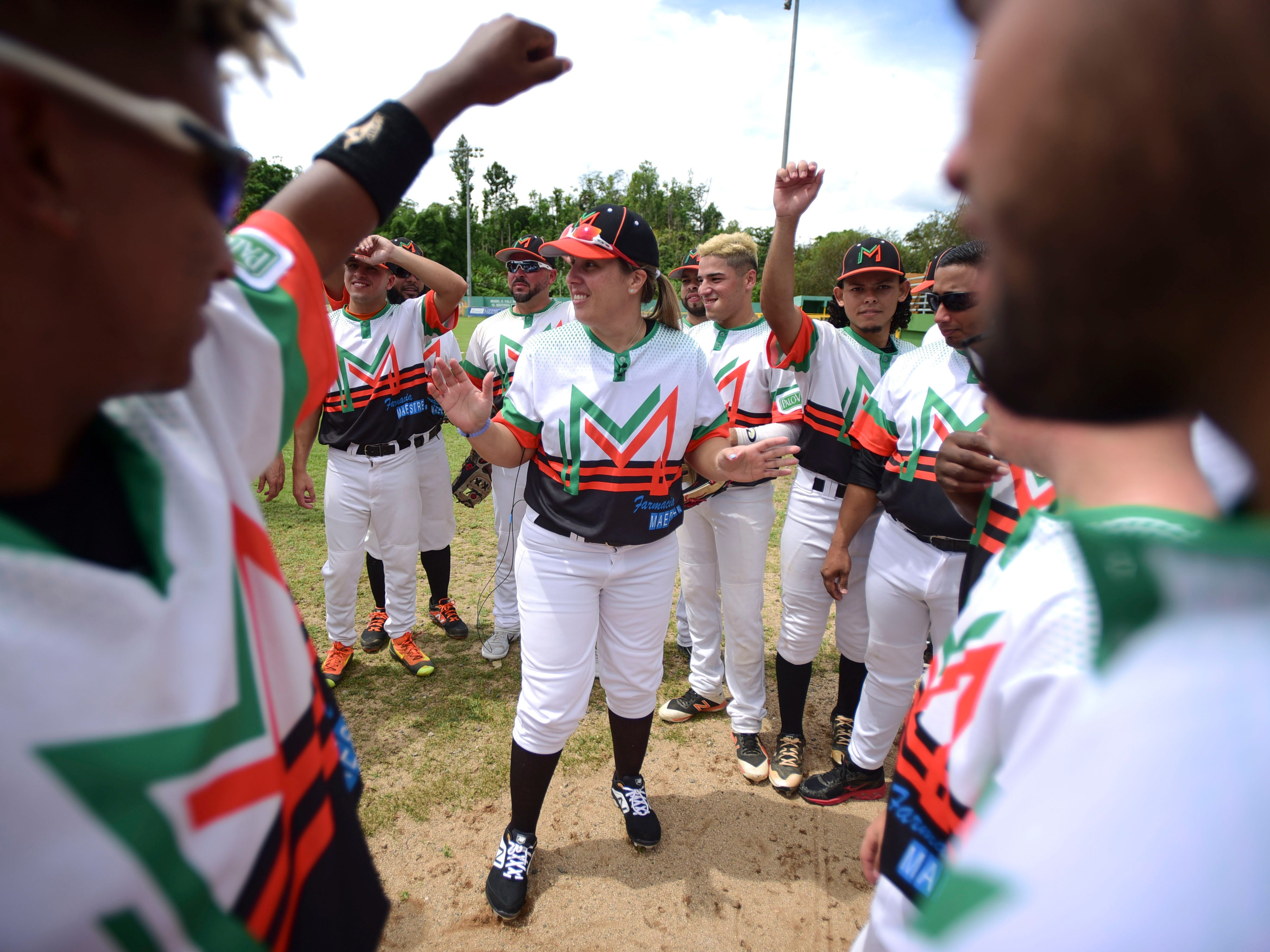 """Diamilette Quiles, center, is welcomed by teammates from the Mountaineers of Utuado baseball team moments before their game against the Patrulleros de San Sebastian at Ramon Cabanas Stadium in Utuado, Puerto Rico, Sunday, May 19, 2019. Quiles, who joined the team days ago, is the first women in Puerto Rico's history to play in an otherwise all-male baseball tournament organized by a popular semi-pro league. """"I'm leaving it all in God's hands,"""" she said."""