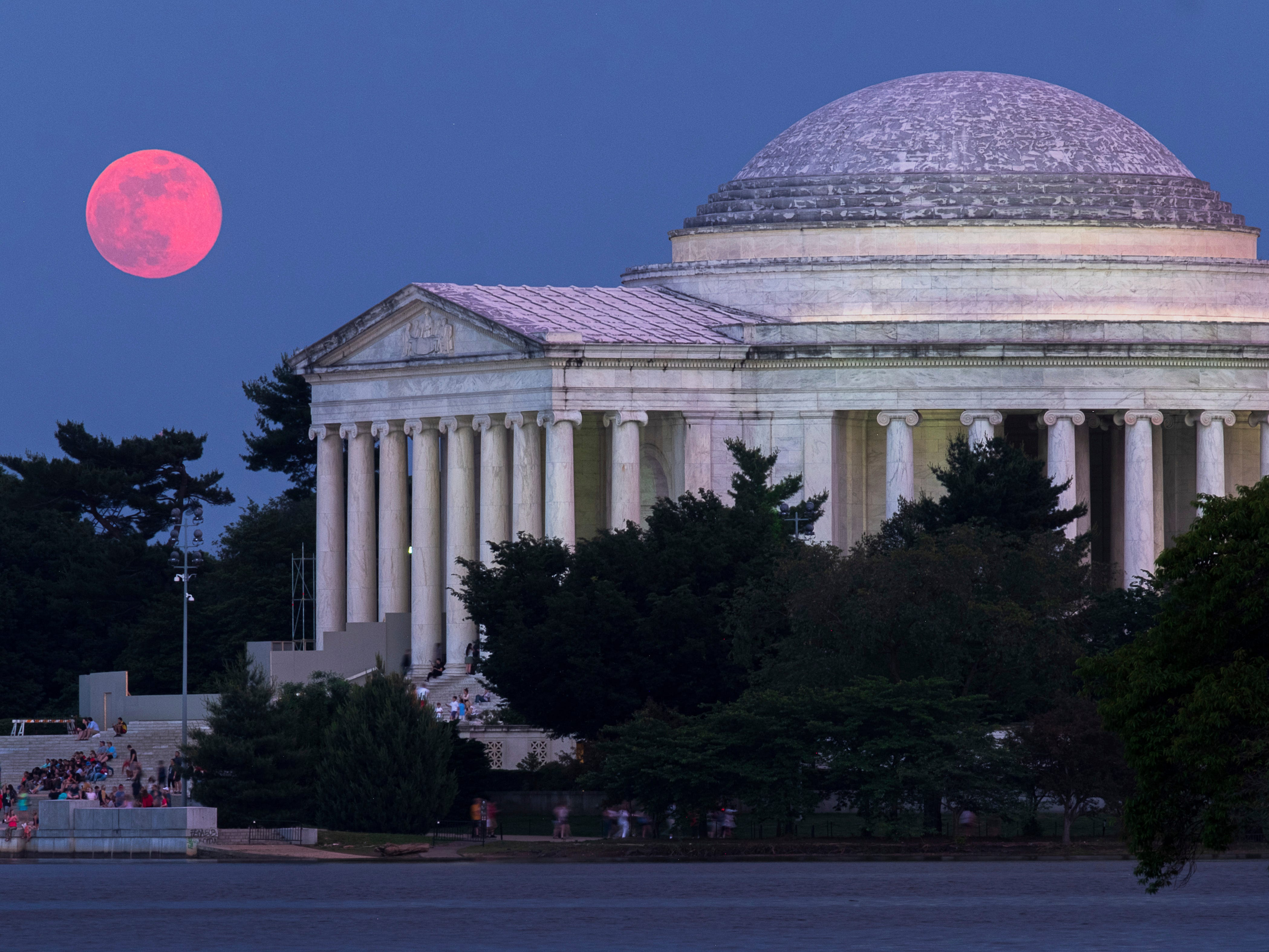 The full moon appears red as it burns through the haze as it rises behind the Jefferson Memorial in Washington Saturday night, May 18, 2019.