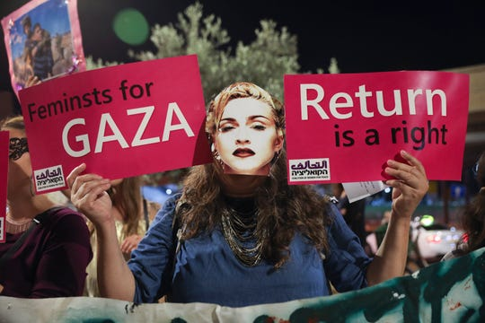 A supporter of the Coalition of Women for Peace wears a mask depicting Madonna during a rally for lifting the Gaza blockade and to boycott the 2019 Eurovision Song Contest in Tel Aviv, Israel, Saturday.
