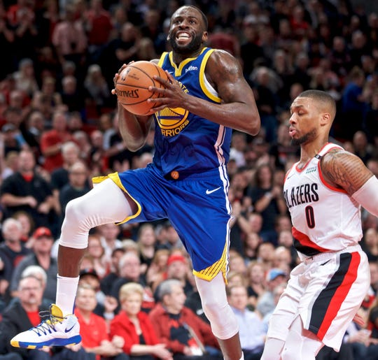 Golden State Warriors forward Draymond Green, left, prepares to shoot over Portland Trail Blazers guard Damian Lillard during the first half.